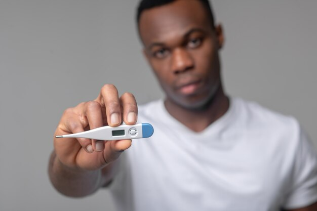 Thermometer, ziekte. trieste jonge man met een donkere huid die thermometer naar de camera steekt terwijl hij op een lichtgrijze achtergrond staat