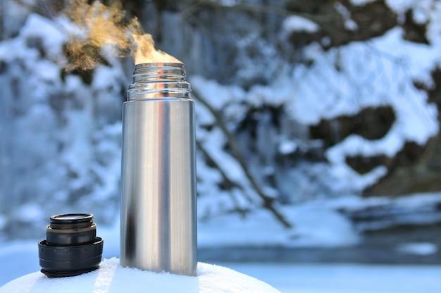 Thermos met een warme drank op berg waterval