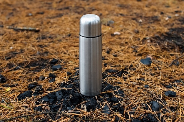 Thermosflessen in het bos staan op kolen