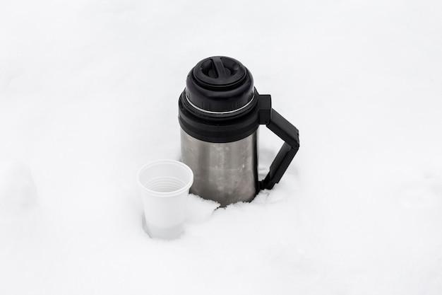 Thermoskan met hete thee en een wegwerpglas in de winter in een sneeuwjacht in de natuur.