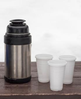 Thermoskan met hete thee en wegwerpglazen in de winter op een bankje in de natuur.