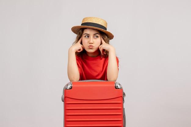 Thpughtful vakantie meisje met haar valise staande op wit