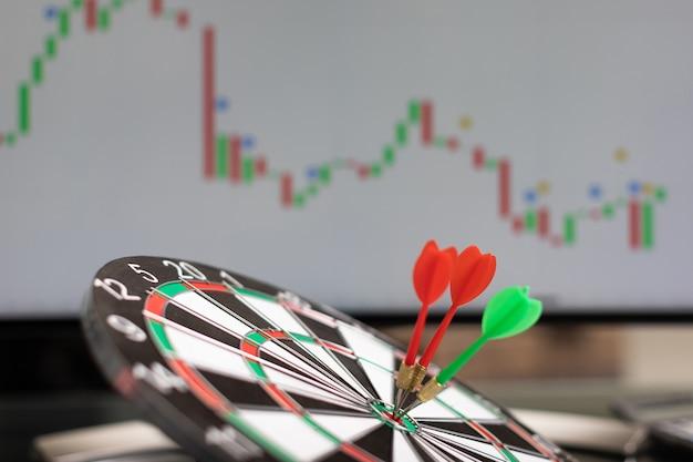 Three darts raken doelwit tegen de achtergrond van een grafiek met beursstatistieken