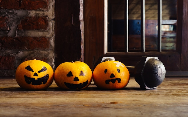 Three oranges with halloween pumpkins face