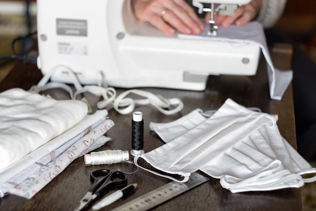 Thuis beschermende antivirusmaskers naaien. vrouw naait maskers op een naaimachine