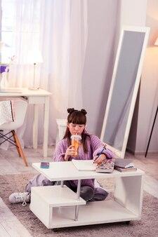 Thuis bezig. attent kind dat aantekeningen maakt terwijl hij water met citroen drinkt
