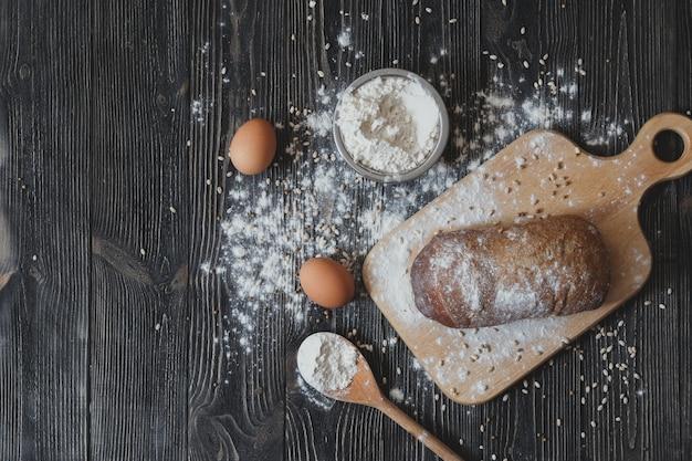 Thuis brood bakken op een rustieke houten tafel met ruimte voor tekstlay-out. uitzicht van boven.