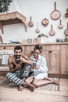 Thuis comfort. donkerhuidige gefocuste vrouw in huiskleren blootsvoets met smartphone en man eten zittend op de keukenvloer