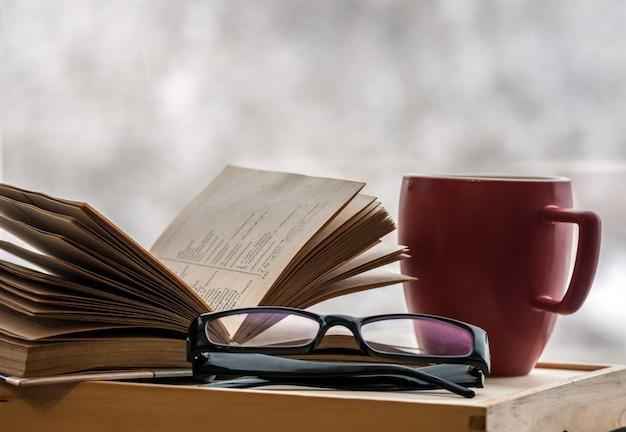 Thuis een oud boek met glazen lezen op een koude de winteravond. thuis een boek lezen met koffie