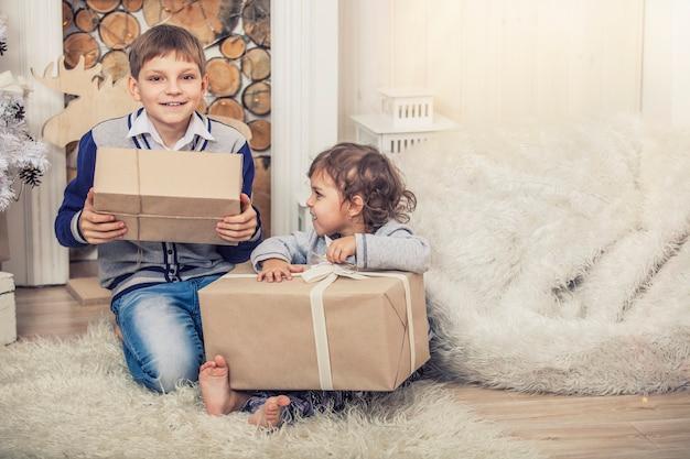 Thuis een vrolijke jongen en meisje met dozen vol cadeautjes in het kerstinterieur