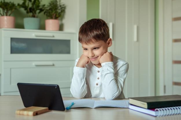 Thuis elektronisch afstandsonderwijs. leuke gelukkige baby die thuiswerk thuis doen die tablet gebruiken.