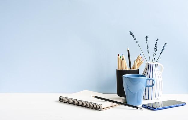 Thuis- en kantoorbureau met kladblok, telefoon, potloden, koffie, op een witte tafel over lichtblauwe muur. mockup met kopieerruimte