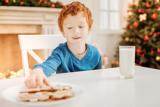 Thuis eten is het beste. vrolijke jongen die lacht terwijl hij aan een tafel zit en zijn aandacht richt op een bord vol peperkoek dat ik gebakken heb door zijn moeder.