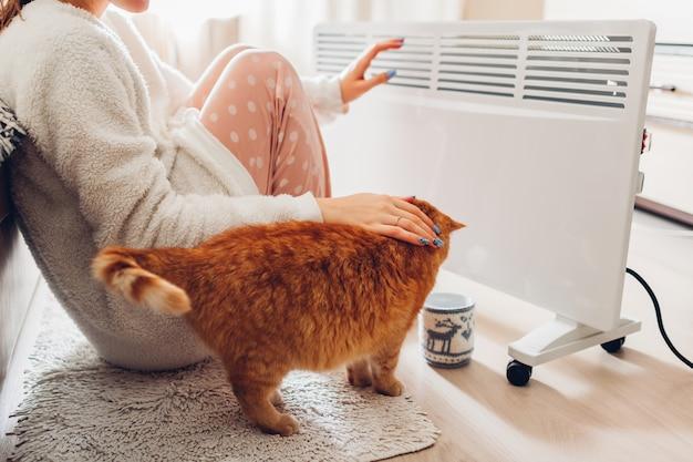 Thuis gebruik van verwarming in de winter. vrouw die haar handen met kat verwarmt. stookseizoen.