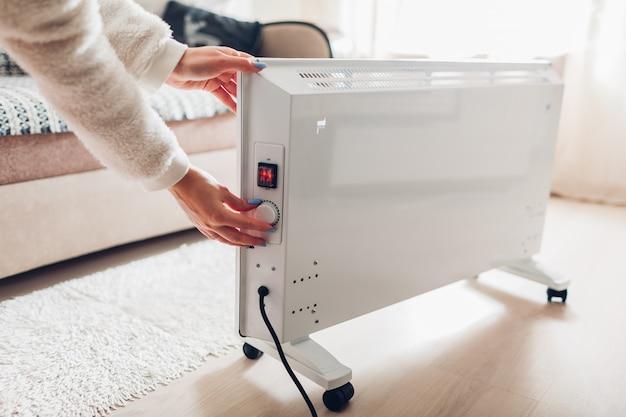 Thuis gebruik van verwarming in de winter. vrouw die temperatuur op verwarmer regelt. stookseizoen.