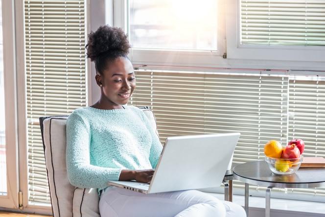 Thuis genieten. mooie jonge glimlachende vrouw die aan laptop werkt en koffie drinkt terwijl thuis het zitten als grote comfortabele voorzitter