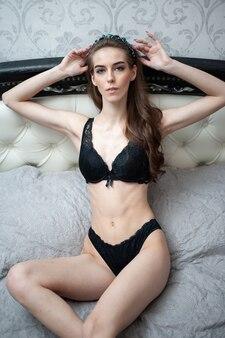 Thuis genieten. mooie jonge natuurlijke schoonheid vrouw ontspannen thuis in lui weekendochtend in gezellige homewear lingerie.