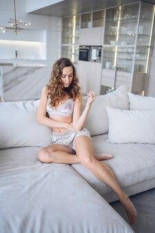 Thuis genieten. mooie jonge natuurlijke schoonheidsvrouw die met krullend haar thuis in luie weekendochtend ontspannen in comfortabele homewearlingerie.