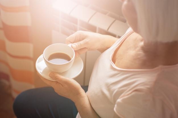 Thuis genieten van koffie. vrouw en koffie in handen die door het glasvenster kijken