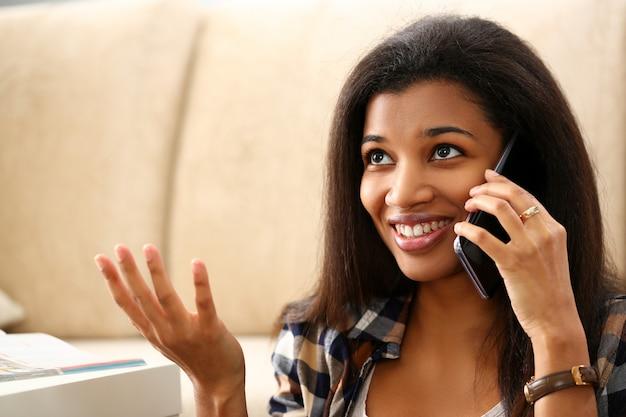 Thuis glimlachend de in hand mobiele telefoon van de zwartegreep