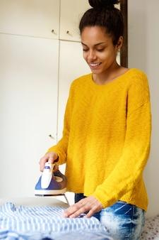Thuis glimlachend jonge vrouw het strijken van kleding