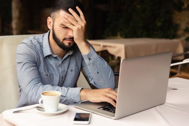 Thuis hard werken, hoofdpijn. de ongelukkige mens houdt zijn hoofd terwijl binnen het werken aan laptop