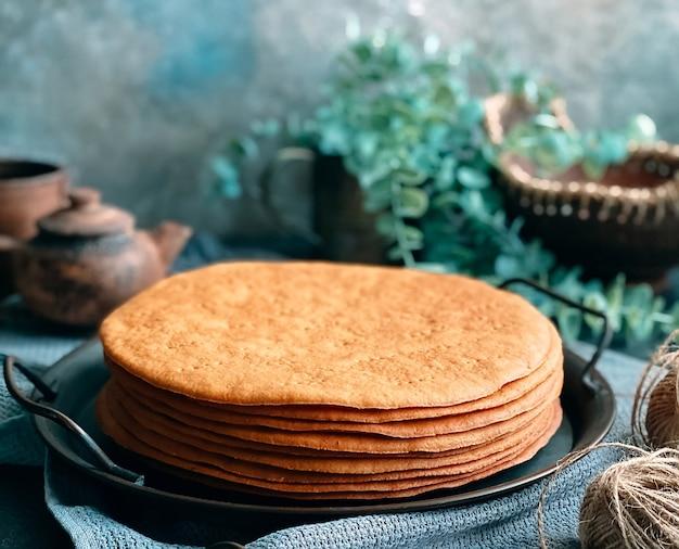 Thuis honingcake koken. ronde gebakken taartlagen gestapeld op plaat.
