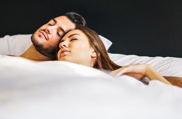 Thuis houdend van jonge paarslaap samen in een bed met witte bladen