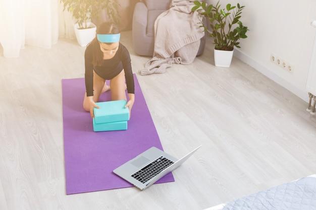 Thuis in quarantaine. klein meisje doet yoga tijdens quarantaine in zelfisolatie