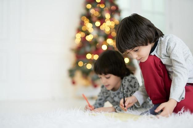 Thuis is het hart van vakantie. twee kleine latijns-jongens, een tweeling die foto's maakt met potloden terwijl ze thuis op de vloer zitten, versierd voor kerstmis. broers en zussen die samen creatieve activiteiten ondernemen