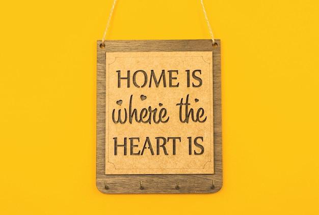 Thuis is waar het hart is, houten plaat voor sleutels, gezellig en schattig woondecoratieconcept, gele achtergrondfoto
