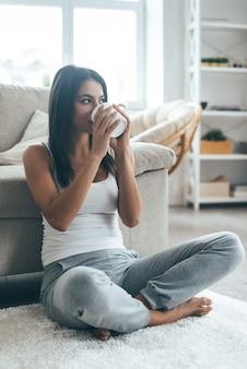 Thuis koffie drinken. aantrekkelijke jonge vrouw die thuis op het tapijt zit en koffie drinkt