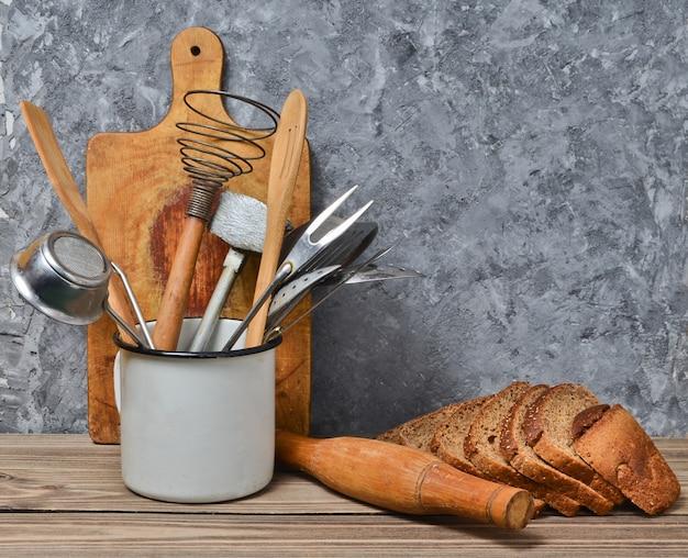 Thuis koken, bakkerij. houten plank, keuken gereedschap, roggebrood op een tafel op de achtergrond van een grijze betonnen muur.