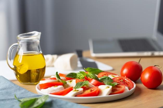 Thuis koken concept. iemand kijkt op computer kookles op internet hoe je caprese salade kookt, is de beroemde italiaanse salade met verse tomaten, mozzarella kaas en basilicum