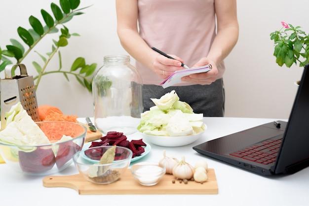Thuis koken een vrouw bekijkt online videorecepten op een laptop en kookt thuis in de keuken