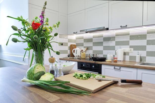 Thuis koken, groenten voor salade kool komkommer groene uien op snijplank met mes, achtergrond keukenmeubels interieur, voedsel bereiden op kookplaat, bloemboeket