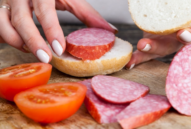 Thuis koken meisjessandwichbroodjes van worst en tomaten