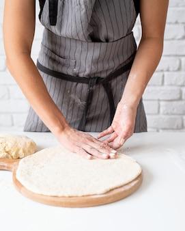 Thuis koken. vrouw kneden deeg thuis voorbereiding pizza
