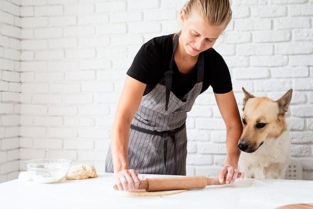 Thuis koken. vrouw kneedt thuis deeg terwijl haar hond erbij zit