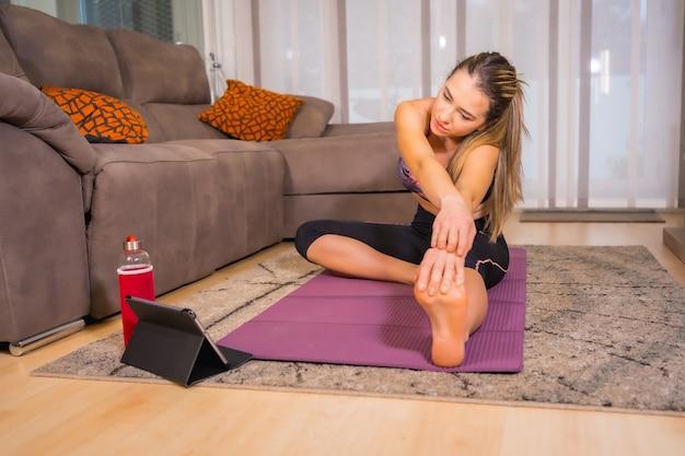 Thuis oefenen met in een online klas, blanke vrouw doet yoga-oefeningen thuis op de mat
