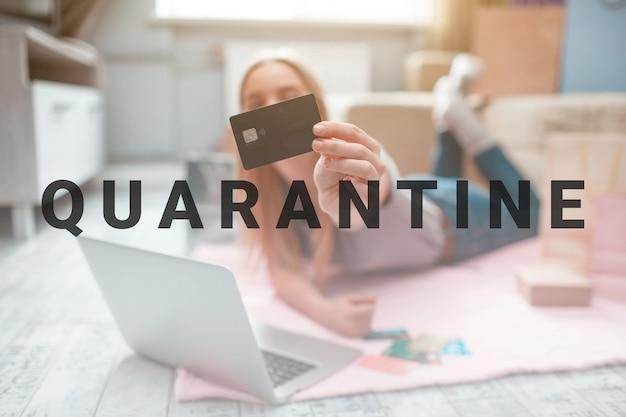 Thuis online winkelen. hand houdt zwarte bankkaart op een achtergrond van een vrouw met laptop