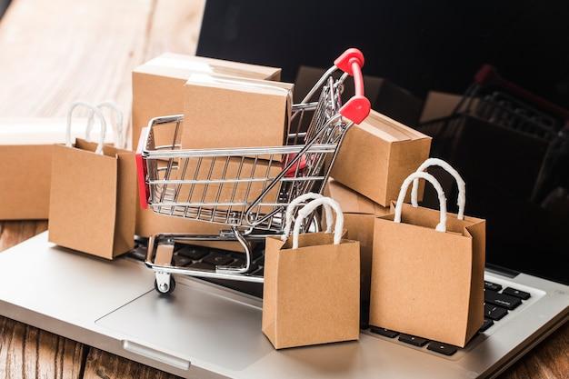 Thuis online winkelen. kartons in een winkelwagentje op een laptop toetsenbord