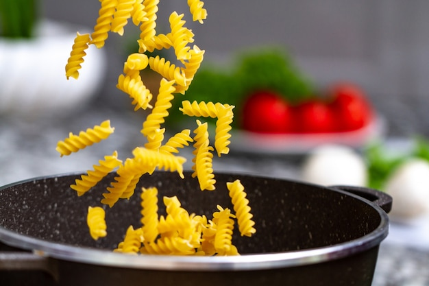 Thuis pasta koken voor een lunch. gietende fusilli in een steelpan