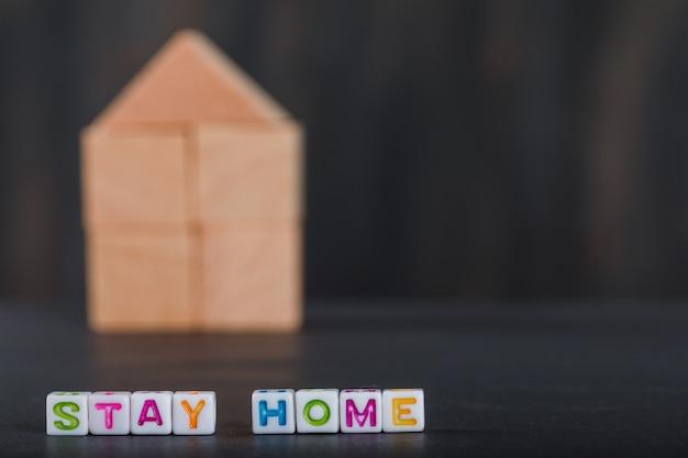Thuis quarantaineconcept met houten huis, witte grijze kubussen.