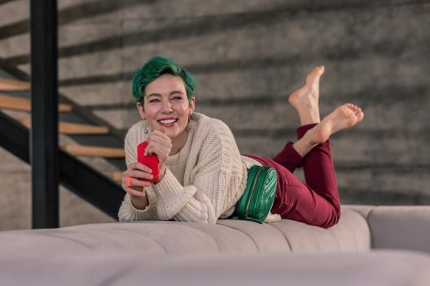 Thuis relaxen. stralende vrouw met groene ogen die thuis op de bank aan het chillen is terwijl ze op haar vriendje wacht