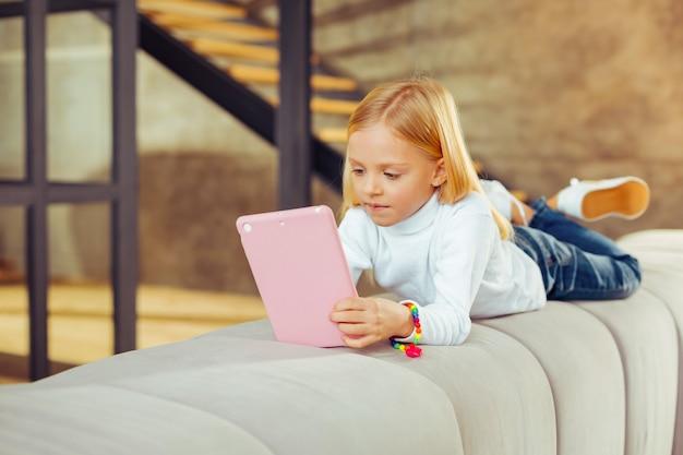 Thuis rust. charmant klein vrouwtje dat op ellebogen leunt en naar het scherm van haar gadget staart