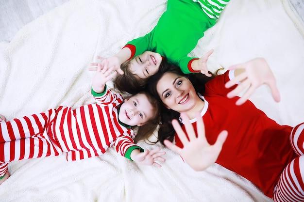 Thuis rust een gezin in gestreepte pyjama uit. kleine kinderen verkleed als elfjes liggen op de bank. een blije familie.