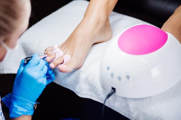 Thuis salon pedicure voetverzorging en nagel het proces van professionele pedicure master in blauwe handschoenen brengt lichtroze gellak aan