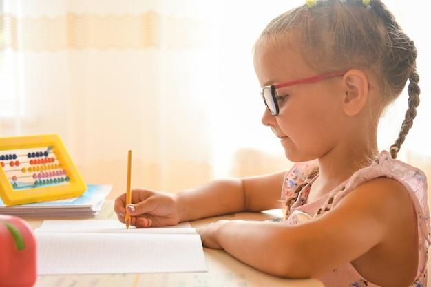 Thuis studeren, portret van een klein jong meisje, zittend aan een bureau met een bril.