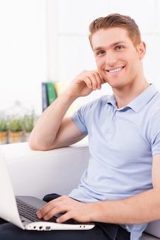 Thuis surfen op het net. knappe jonge man zittend op de bank en werkend op laptop
